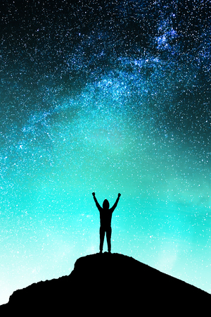Backlit person on hill standing on beautiful starry night sky space background. Purpose and emotive concept Stock Photo