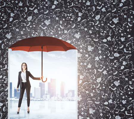 Young businesswoman standing under umbrella on abstract background with city and business sketch on concrete wall. Insurance and management concept