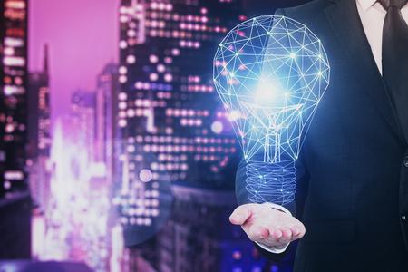 Lampe polygonale rougeoyante à la main d'homme d'affaires sur fond de ville de nuit floue. Concept d'innovation et d'idée. Double exposition