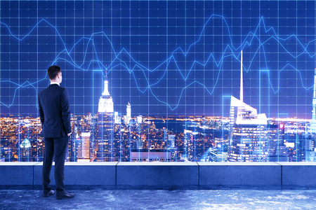 Young businessman on rooftop with forex chart grid and glowing night new york city background. Investment and market concept. Double exposure Stock Photo