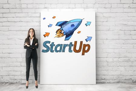 Retrato de mujer de negocios joven y atractiva con los brazos cruzados de pie junto al dibujo del cohete sobre fondo de pared de ladrillo blanco con gran pancarta. Concepto de puesta en marcha y logro