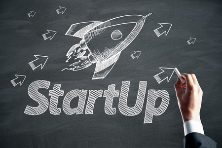 Businessman hand drawing creative rocket sketch on chalkboard wall background. Startup and accelerate concept Stockfoto