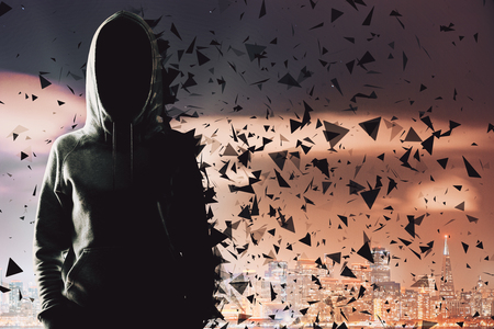 Abstract polygonal hacker in hoodie on blurry night city and sky background. Malware and theft concept Stok Fotoğraf