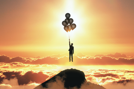Backlit person flying with balloons on orange sunset sky with clouds background. Freedom and success concept