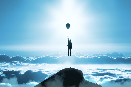 Backlit person flying with balloons on blue sunset sky with clouds background. Freedom and abstraction concept