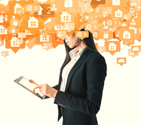 Side view of young businesswoman using tablet with abstract house and message icons on white background. Communication and automation concept