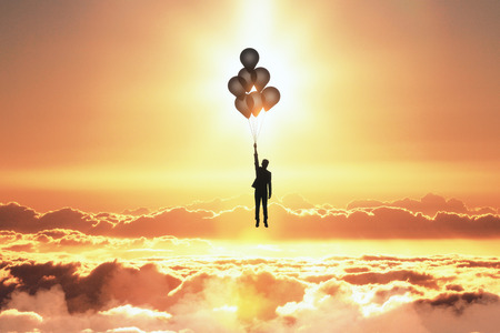 Backlit person flying with balloons on orange sunset sky with clouds background. Freedom and purpose concept
