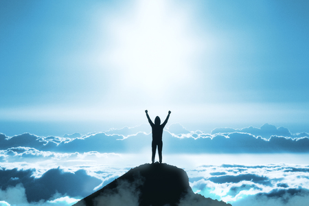 구름 배경으로 푸른 하늘에 산 정상에 서 있는 젊은 백라이트 사람의 후면 보기. 성공과 리더십 개념
