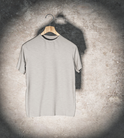Clean grey t-shirt in spotlight hanging on concrete wall. Mockup and fashion concept. 3D Rendering