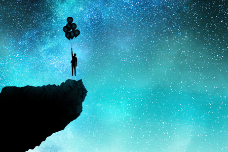 Businessman silhouette with balloon on cliff standing on beautiful starry sky background. Freedom and solution concept