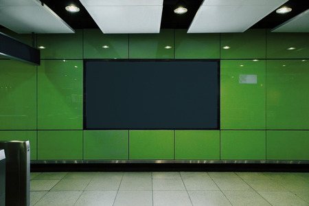 Front view of empty black poster in green underground subway station. Commercial and ad concept. Mock up