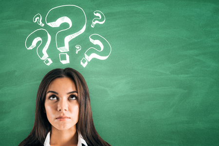 Portrait of attractive young european businesswoman with question mark drawings on green background. Confusion and ask concept