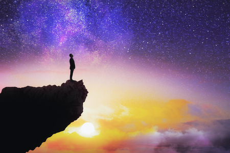 Tiny man silhouette on cliff standing on beautiful starry sky background with sunset. Purpose and way concept