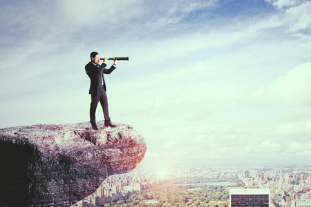 Side view of young businessman on cliff using telescope to look into the distance on city background. Research and research concept