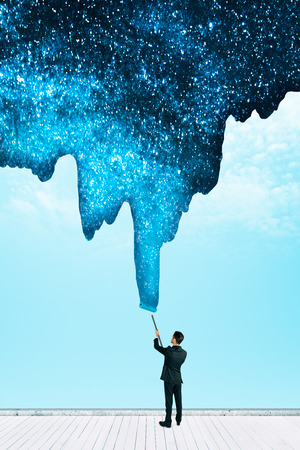 Businessman drawing beautiful starry sky on blue background. Creativity and emotive concept Stockfoto