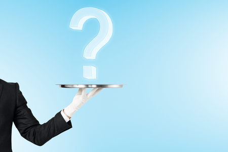 Hand holding tray with question marks on blue background. Quiz and ask concept