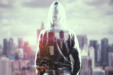 Hacker on blurry city background. Criminal and thief concept. Double exposure