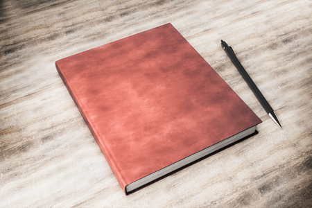 Blank closed red hardcover book and pen on wooden desktop background. Mock up, 3D Rendering