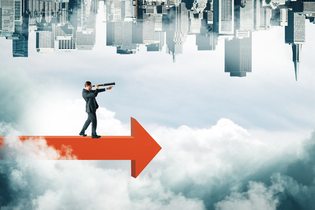 Businessman looking into the distance with binoculars on red arrow on abstract sky background with clouds and upside-down city skyline. Growth and vision concept