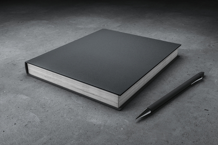 Blank closed black hardcover book and pen on concrete desktop background. Mock up, 3D Rendering
