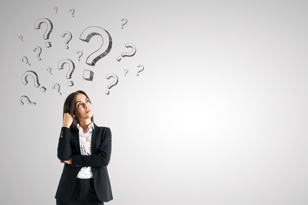 Attractive young european businesswoman with drawn question marks on subtle background. Ask and confusion concept Stock Photo