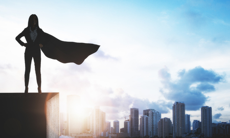 Backlit superhero businesswoman with waving cape standing on rooftop on city and sky background. Copy space. Leadership and confidence concept