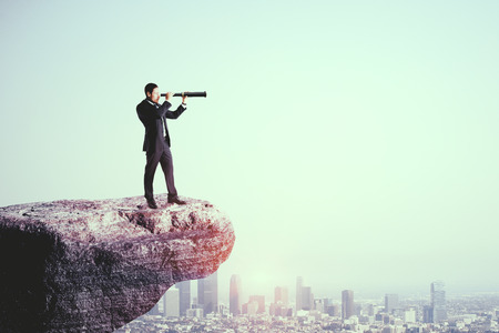 Side view of young businessman on cliff using telescope to look into the distance on city background. Research and success concept