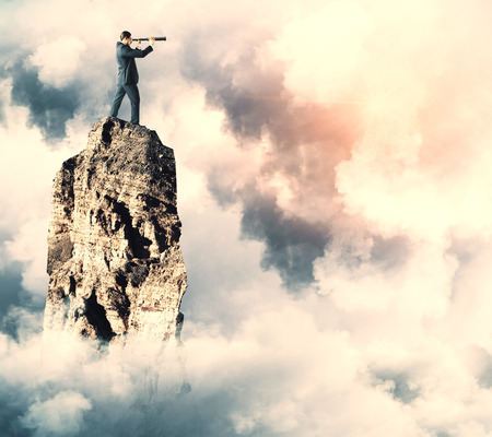 Side view of young businessman on cliff using telescope to look into the distance on cloudy sky background. Forecast and vision concept. Copy space Stok Fotoğraf