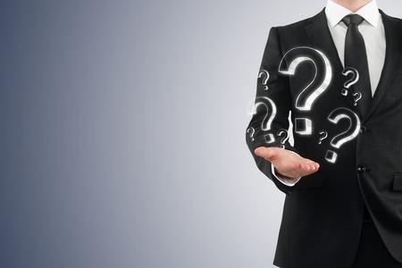 Unrecognizable businessman holding drawn question marks. FAQ and quiz concept