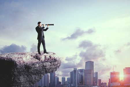 Side view of young businessman on cliff using telescope to look into the distance on city background. Research and vision concept Stok Fotoğraf