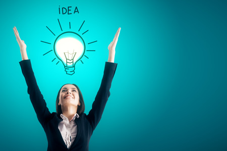 Attractive happy young businesswoman with drawn lamp on blue background. Idea and success concept