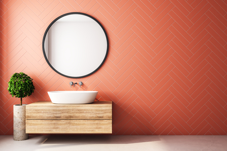 Modern orange bathroom interior with decorative tree, sink, round mirror, sunlight and copy space. 3D Rendering Foto de archivo - 118913637