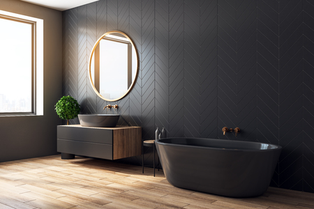 Side view of black orange bathroom interior with decorative tree, bath tub, sink, round mirror, sunlight and copy space. 3D Rendering