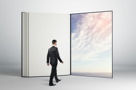 Businessman walking through abstract open book with beautiful sky view. Dream and future concept