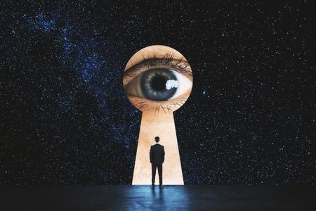 Vue arrière d'un homme d'affaires regardant un trou de serrure abstrait avec un œil sur fond de ciel étoilé. Concept de vision et de but