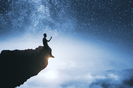 Black backlit young guy silhouette sitting on cliff edge and starry night sky cosmos background. Purpose and success concept Фото со стока