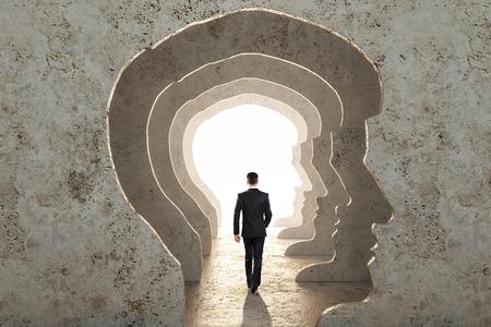 Achteraanzicht van zakenman wandelen in abstracte betonnen man hoofd gang met licht. Abstractie en manierconcept.