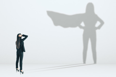 Young businesswoman with superhero shadow on concrete wall background. Confidence and success concept Stockfoto