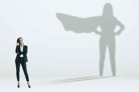 Pretty businesswoman with superhero shadow on concrete wall background. Confidence and success concept Stock Photo