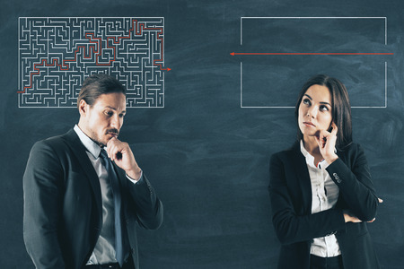 Businessman and woman with maze sketch on chalkboard background. Challenge and solution concept