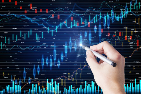 Hand using glowing forex screen on dark background with candlestick chart. Finance and investment concept
