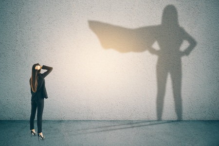 Doordachte zakenvrouw met superheld schaduw op betonnen muur achtergrond. Vertrouwen en succes concept Stockfoto