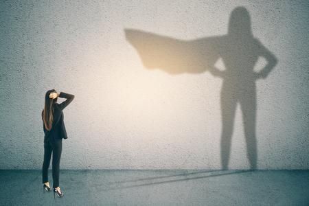 Empresaria pensativa con sombra de superhéroe sobre fondo de muro de hormigón. Concepto de confianza y éxito Foto de archivo