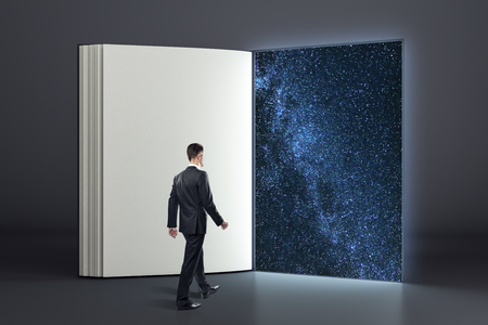 Businessman entering abstract open book into open space. Mystery and success concept.