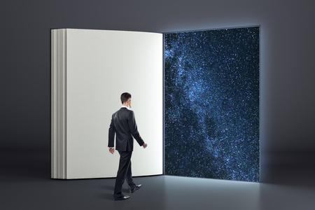Geschäftsmann, der abstraktes offenes Buch in den offenen Raum eingibt. Geheimnis und Erfolgskonzept.