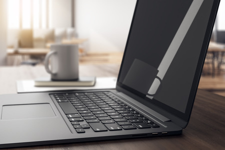 Side view of empty black laptop with reflections on wooden desk with coffee cup, supplies and other items on blurry office interior background. Mock up, 3D Rendering