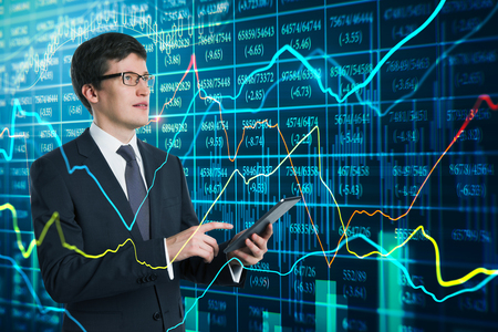Attractive young european businessman using device with glowing forex chart. Technology, network and invest concept. Double exposure