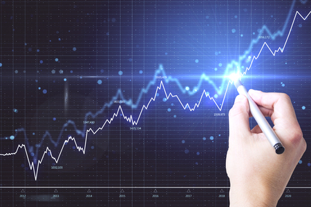 Hand using glowing forex screen on dark wallpaper with candlestick chart. Finance and investment concept