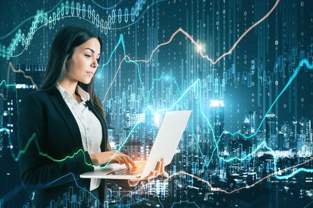Attractive european businesswoman using laptop with forex chart on blurry binary code glowing night city background. Technology and trade concept. Double exposure Stok Fotoğraf
