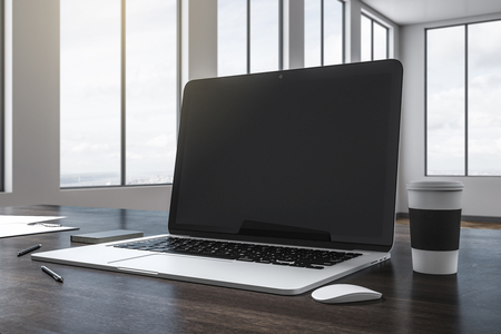 Close up of empty black laptop on wooden desktop with coffee cup and supplies. Blurry office with sky view background. Mock up, 3D Rendering